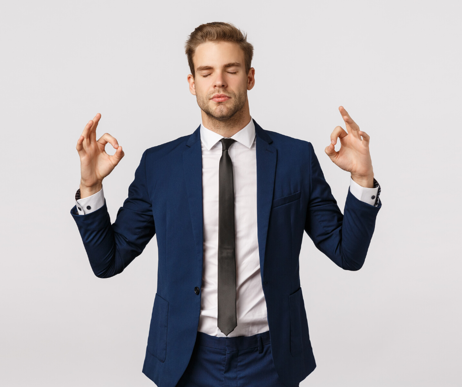 "Man in suit taking a calming breath with fingers in ""om"""